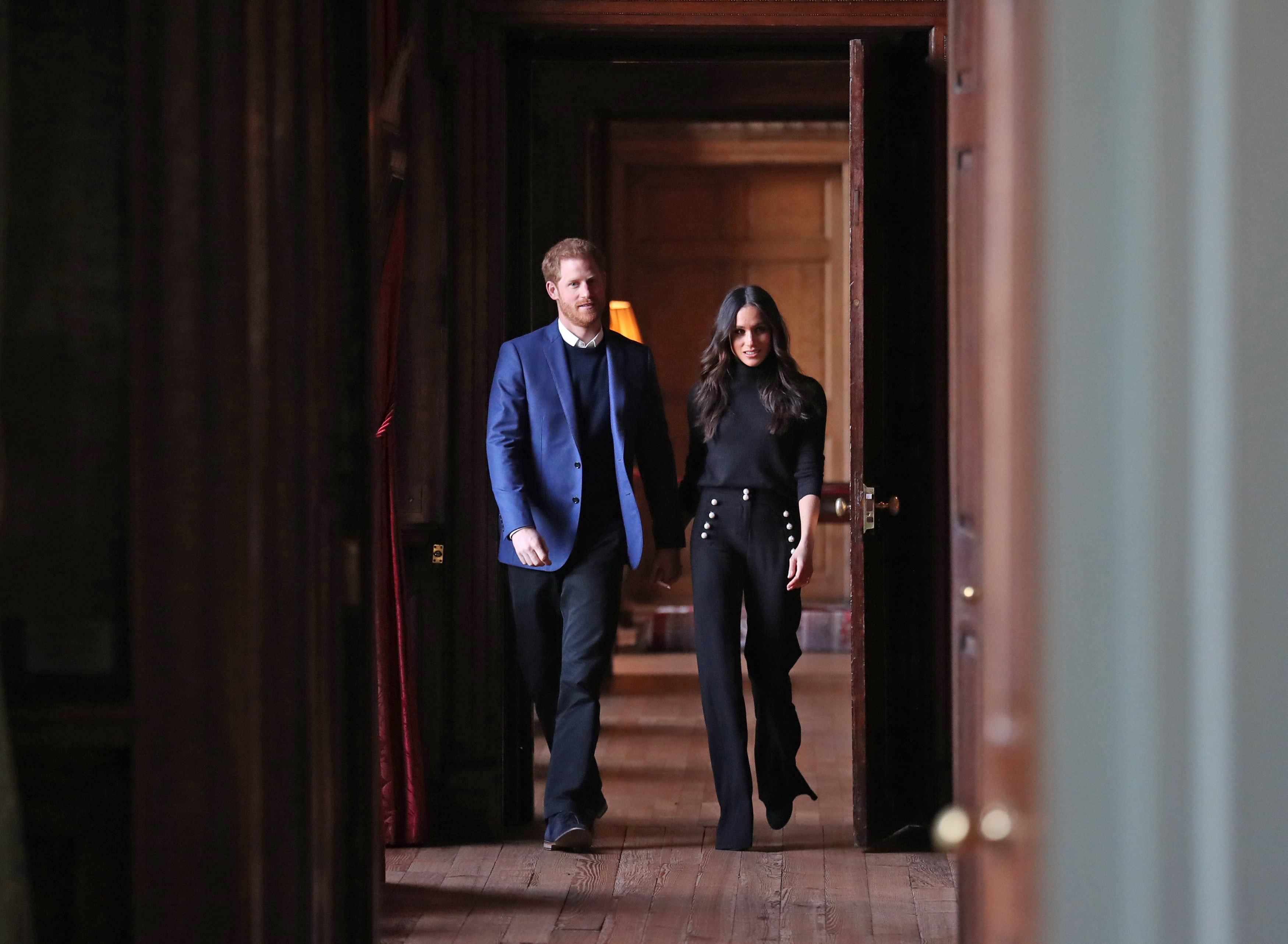 Prince Harry and Meghan Markle walk through the corridors of the Palace of Holyroodhouse.