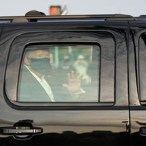 Donald Trump thanks his supporters in a surprise drive-by outside the hospital where he is being treated for COVID-19.