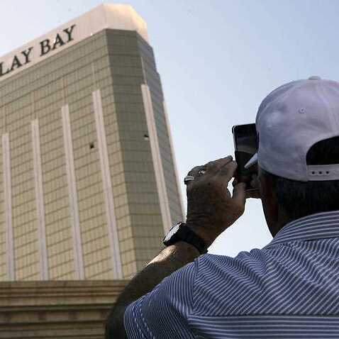 A tourist takes a photo of the broken out windows at the Mandalay Bay hotel on Wednesday, Oct. 4, 2017, in Las Vegas. A gunman opened fire on an outdoor music concert on Sunday killing dozens and injuring hundreds, from the windows.