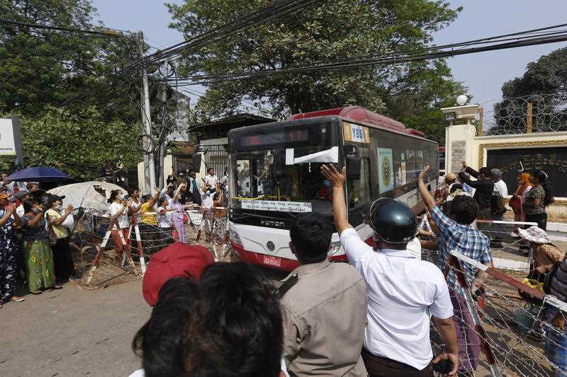 A bus with arrested protesters driven out of Insein prison is greeted by waving civilians.