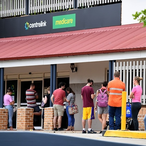 People are seen waiting in line at a Centrelink office