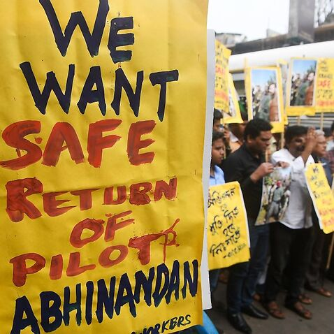 Congress activists shout slogans against Pakistan as they hold posters and pictures of captive Indian Air Force pilot