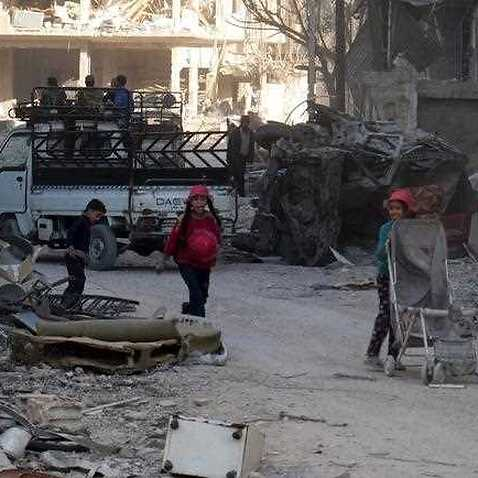 Children walk through the rubble of damaged buildings in the recently-liberated Harasta City, Syria.
