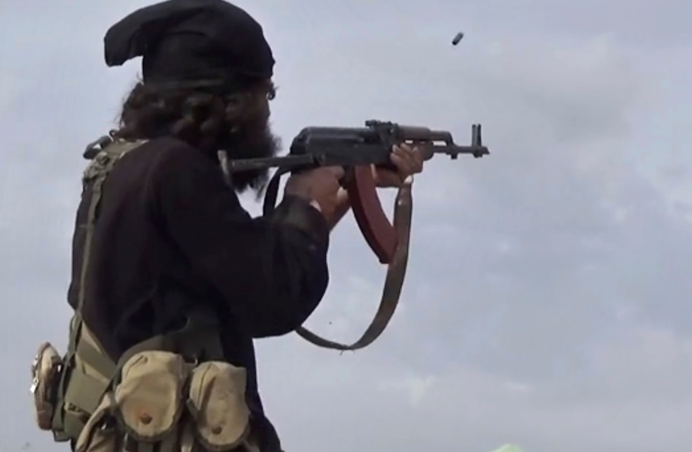 File frame grab from video posted on Monday, March 18, 2019, by the Aamaq News Agency, shows an IS fighter firing his weapon.