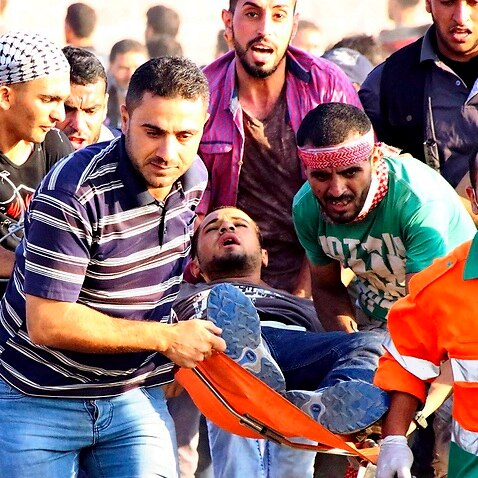 Palestinian people carry a man injured in shooting against Israel army in Gaza strip on May 15, 2018.