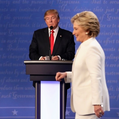 Republican nominee Donald Trump waits behind his podium as Democratic presidential nominee Hillary Clinton makes her way off the stage on Oct 19