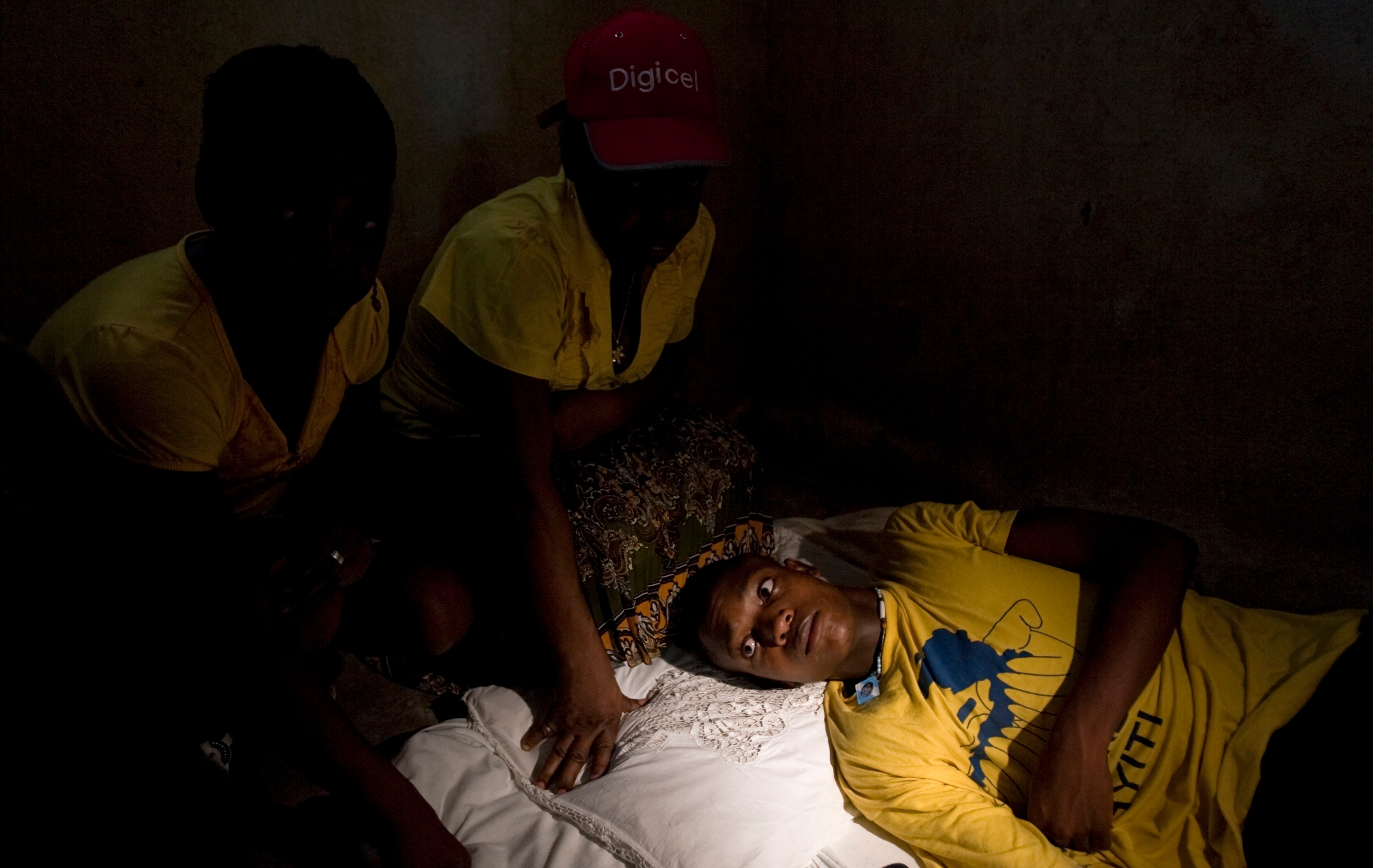 In this picture taken 2011, surrounded by relatives, an 18-year-old man who claims he was sexually abused by Uruguayan peacekeepers lies on his bed in Haiti.