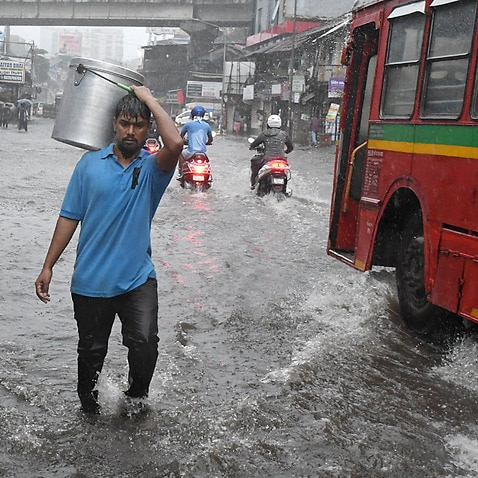 People wade through a flooded street due to heavy rain caused by cyclone Tauktae in Mumbai.