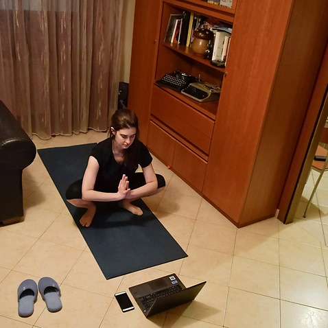 A person follows an online yoga class from her home