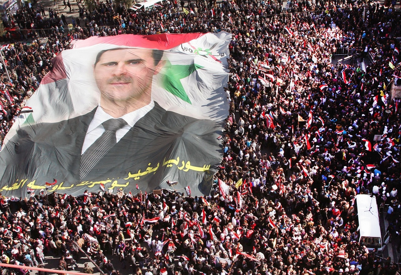 Pro-Syrian regime protesters carry a huge portrait of Syrian President Assad in 2011.