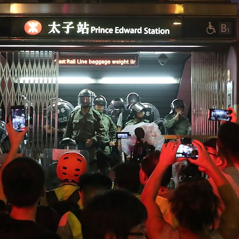 Police officers stand at the entrance to a subway station in Hong Kong.