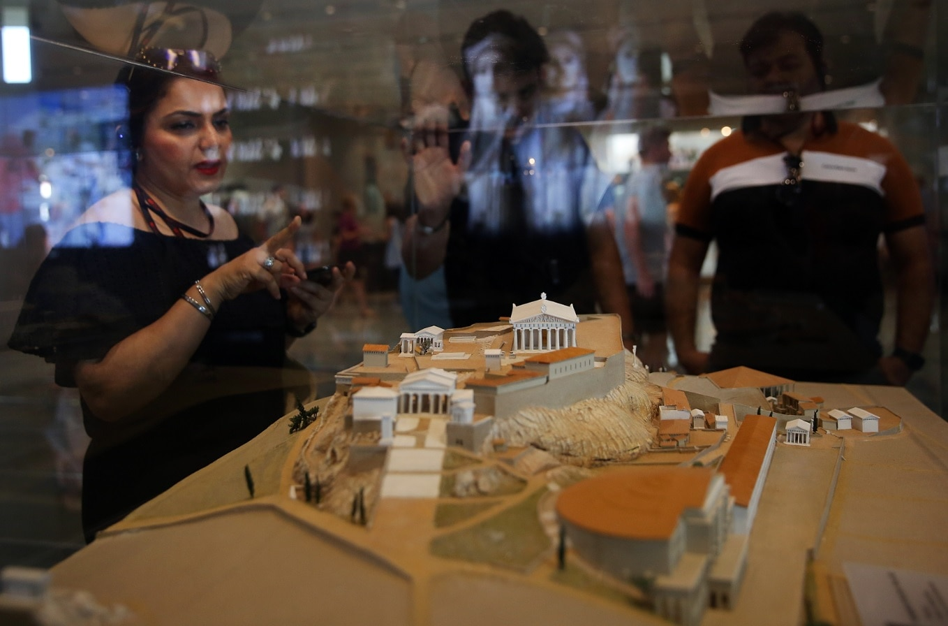 Tourists look at a maquette of the Acropolis Hill as they visit the Museum of Acropolis in Athens, Greece, 21 June 2019,