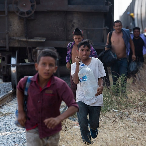 Central American migrants run for a parked train during their journey toward the US-Mexico border, in Ixtepec, Oaxaca state, Mexico.