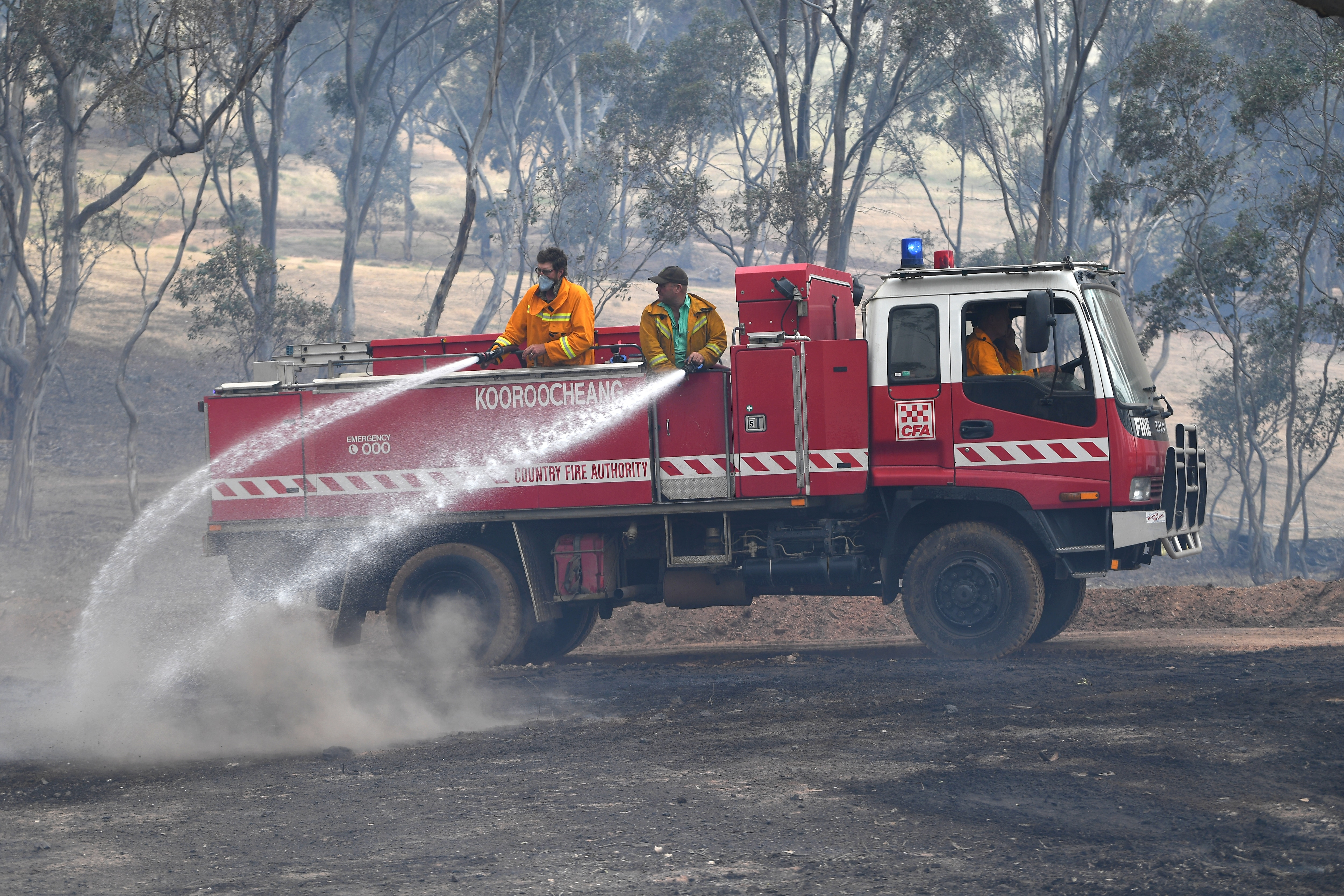 CFA firefighters are seen spraying water onto smouldering bushland at Mount Glasgow, Victoria.