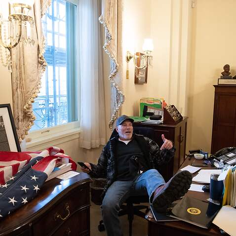 Richard Barnett sits inside the office of US Speaker of the House Nancy Pelosi during a riot at the US Capitol in Washington, DC, on 6 January.
