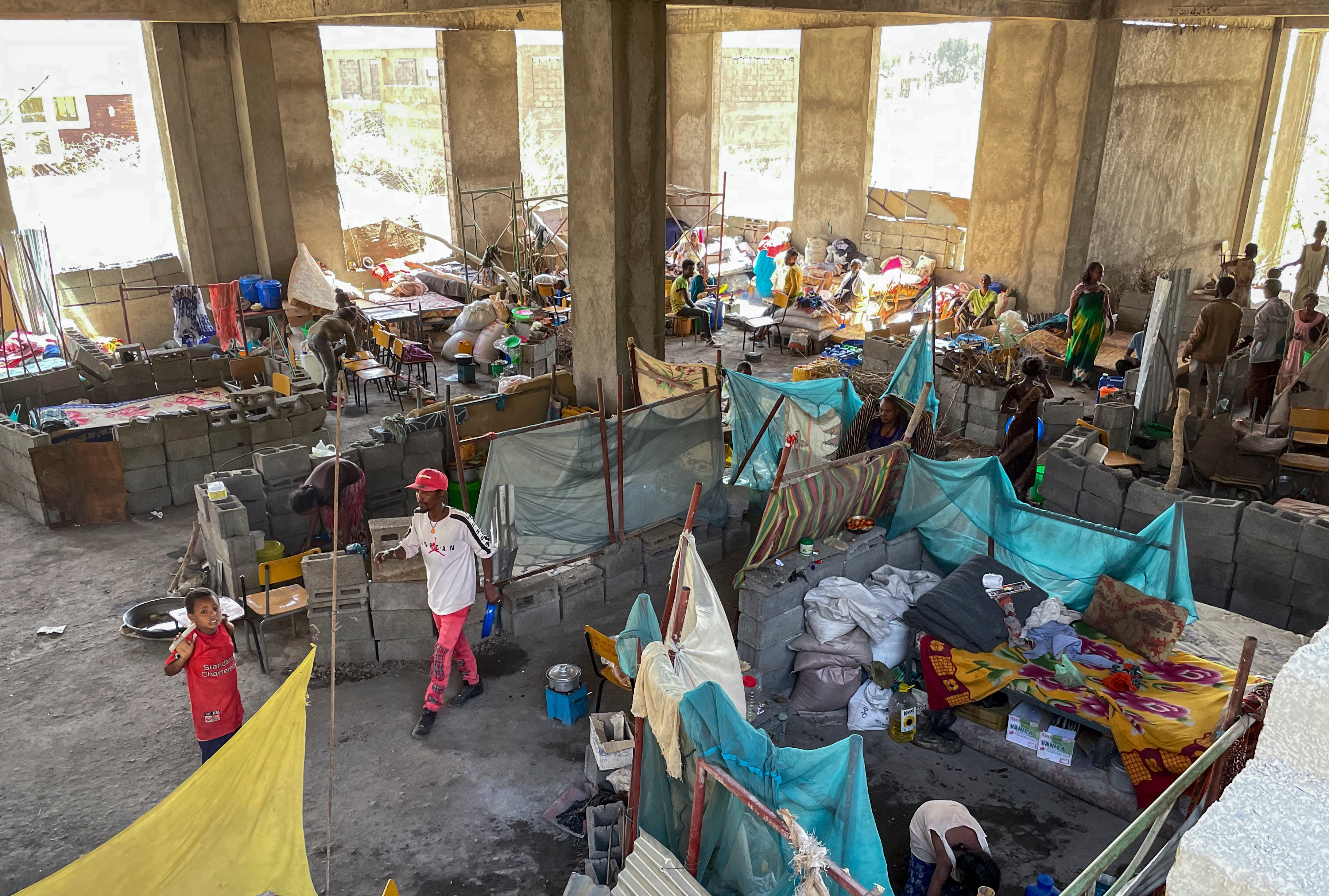 People displaced by the conflict live in crowded conditions in a derelict building of Axum University, in the Tigray region, Tuesday, Feb. 23, 2021.
