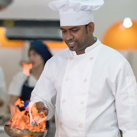 Cherful chef doing a flambe meat looking very happy