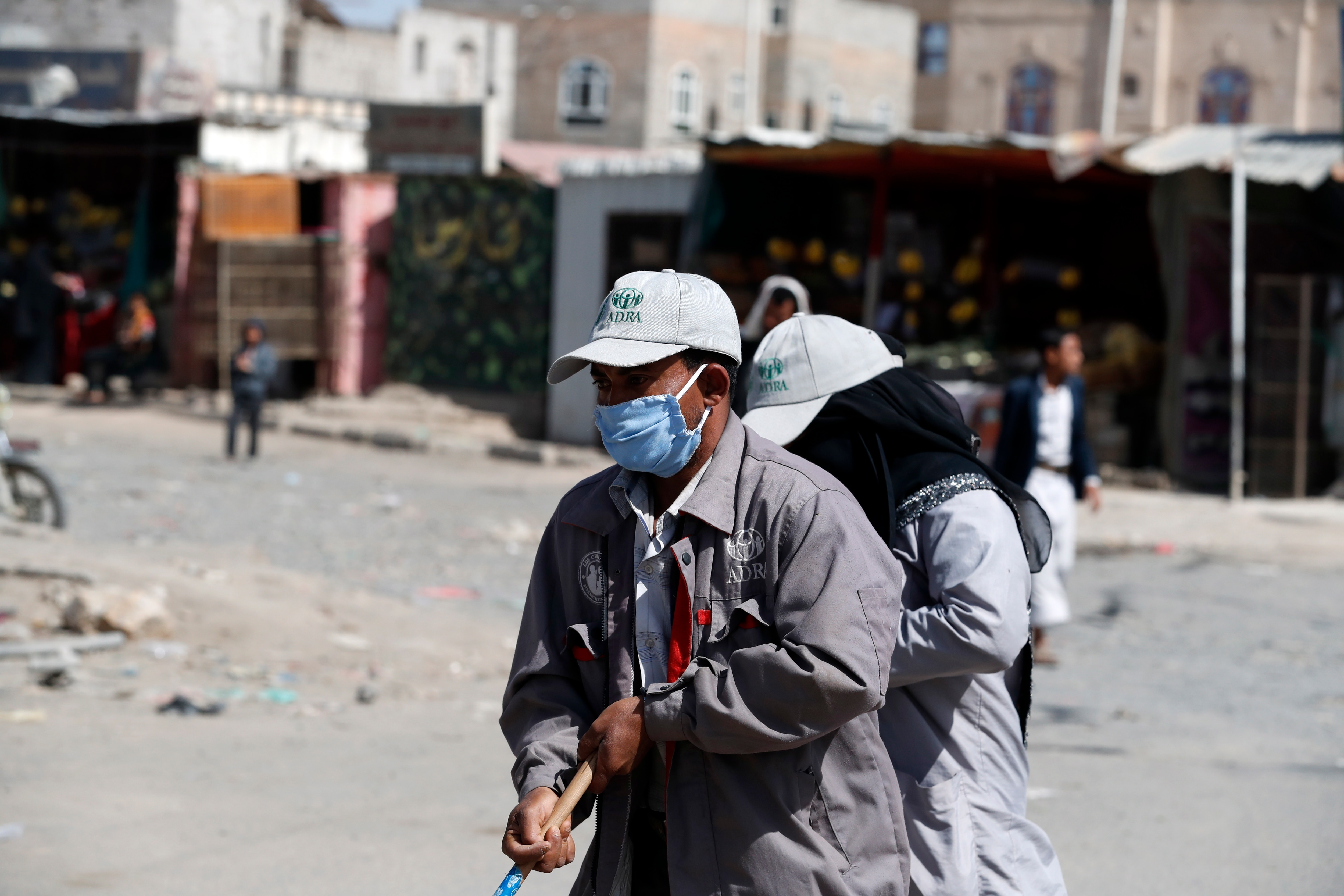 Workers clean a street at a neighbourhood, in Sanaa, Yemen, 7 April 2020.