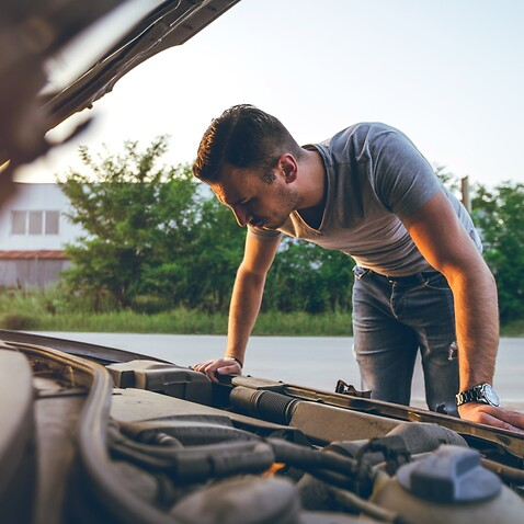 Young man looking under the car hood