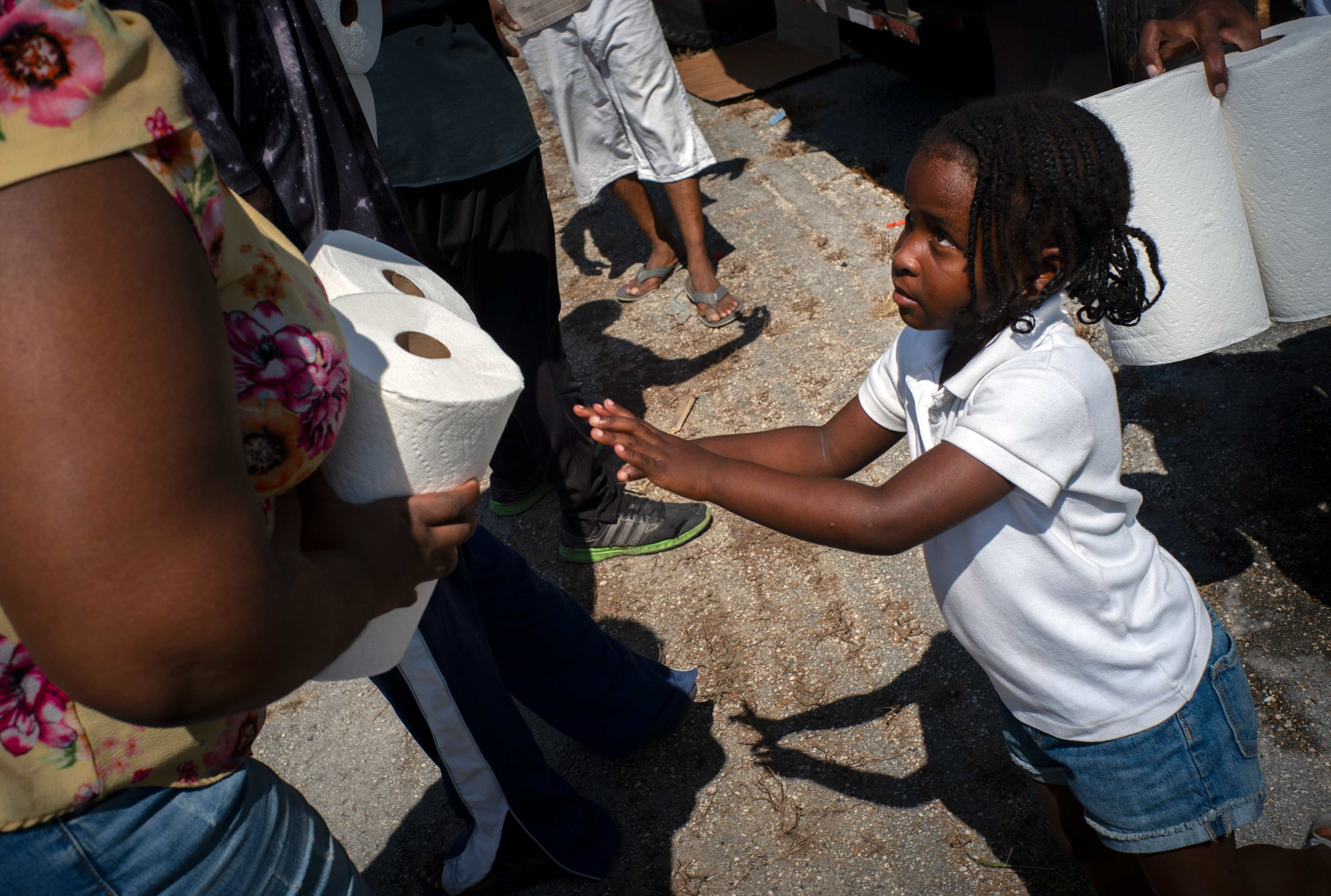 Five-year-old Cattleya Aranha helps to distribute paper rolls donated by private entities to victims of Hurricane Dorian, in Freeport, Bahamas.
