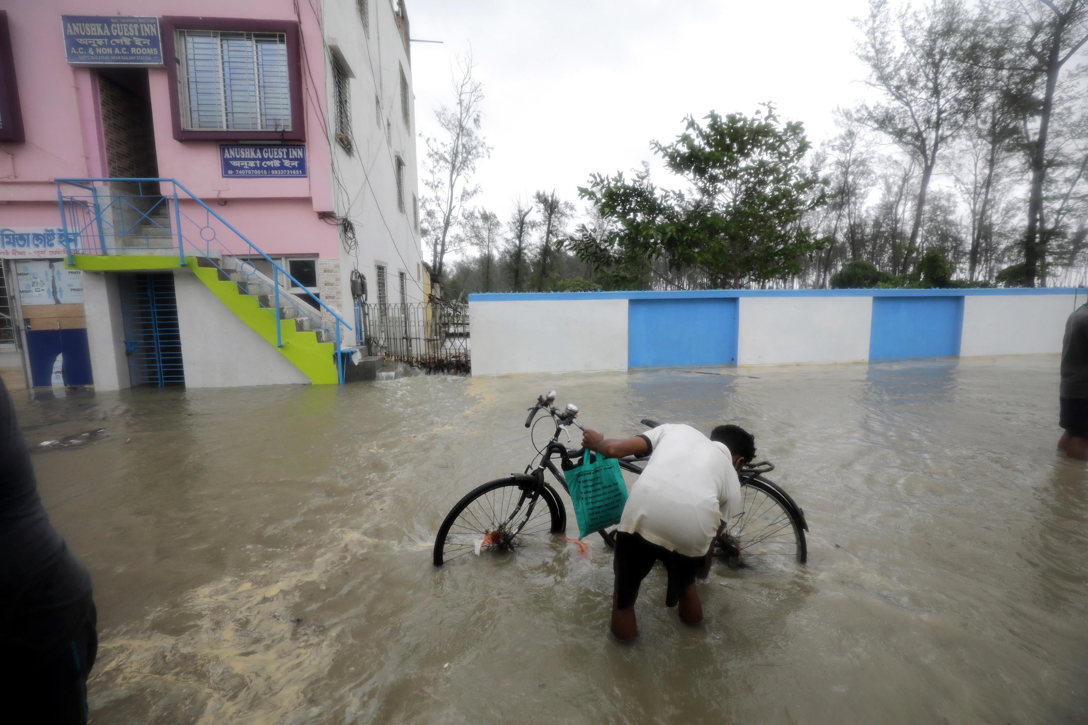 A commuter wades through flooded streets as Cyclone Yaas makes landfall in Digha, near the Bay of Bengal, south of Kolkata, India, 26 May 2021.