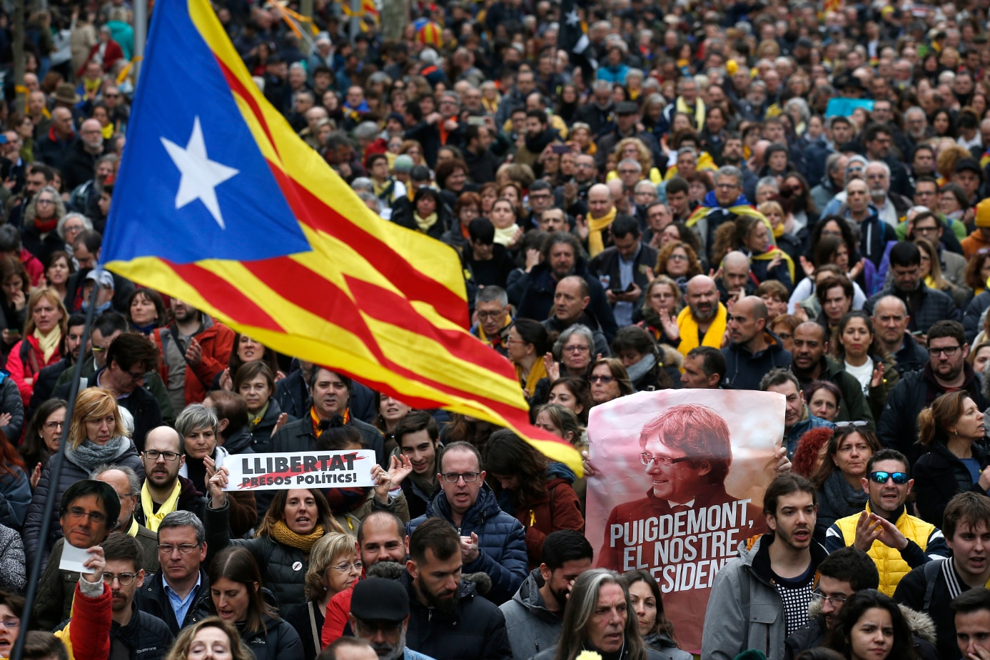 """Protesters in Barcelona carried Catalonia flags and posters reading """"Puigdemont, our President""""."""