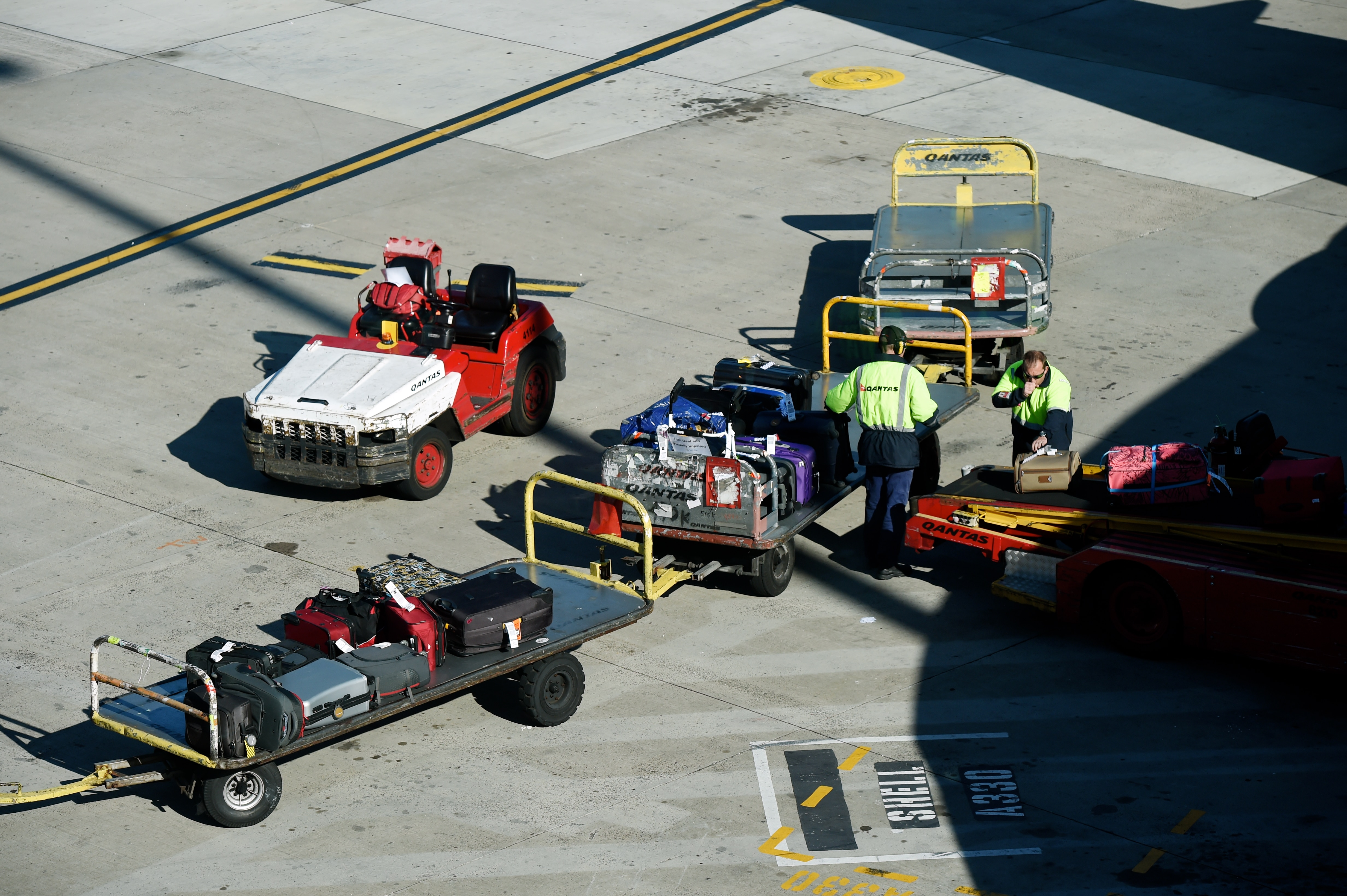 Baggage handlers unload luggage from a QANTAS plane at the domestic terminal in Sydney, Wednesday, July 2, 2014