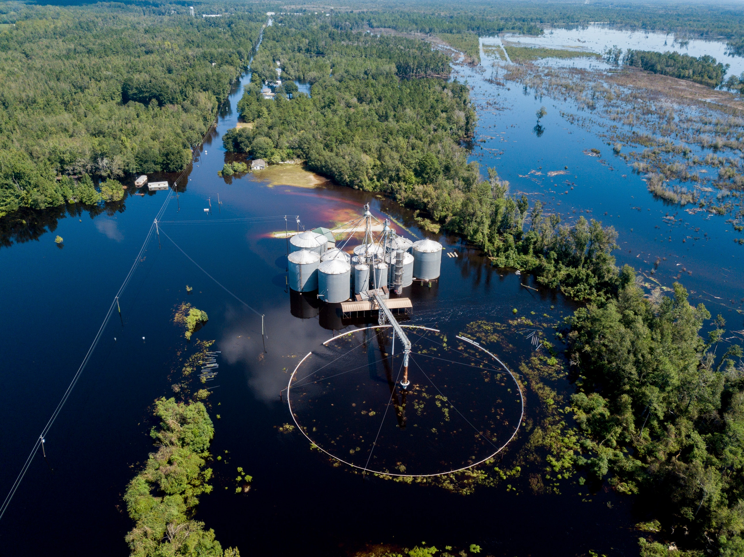 A flooded grain business along Highway 76, which follows the power lines at left, where law enforcement were searching for a submerged van near Nichols, S.C.,