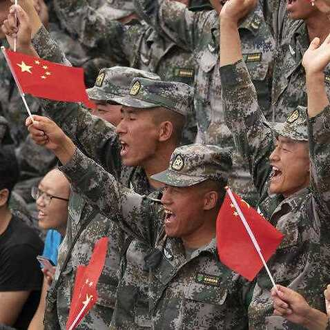 Chinese PLA soldiers hold national flags.  The head of parliament's intelligence committee has warned Australia is facing an increased Chinese threat.