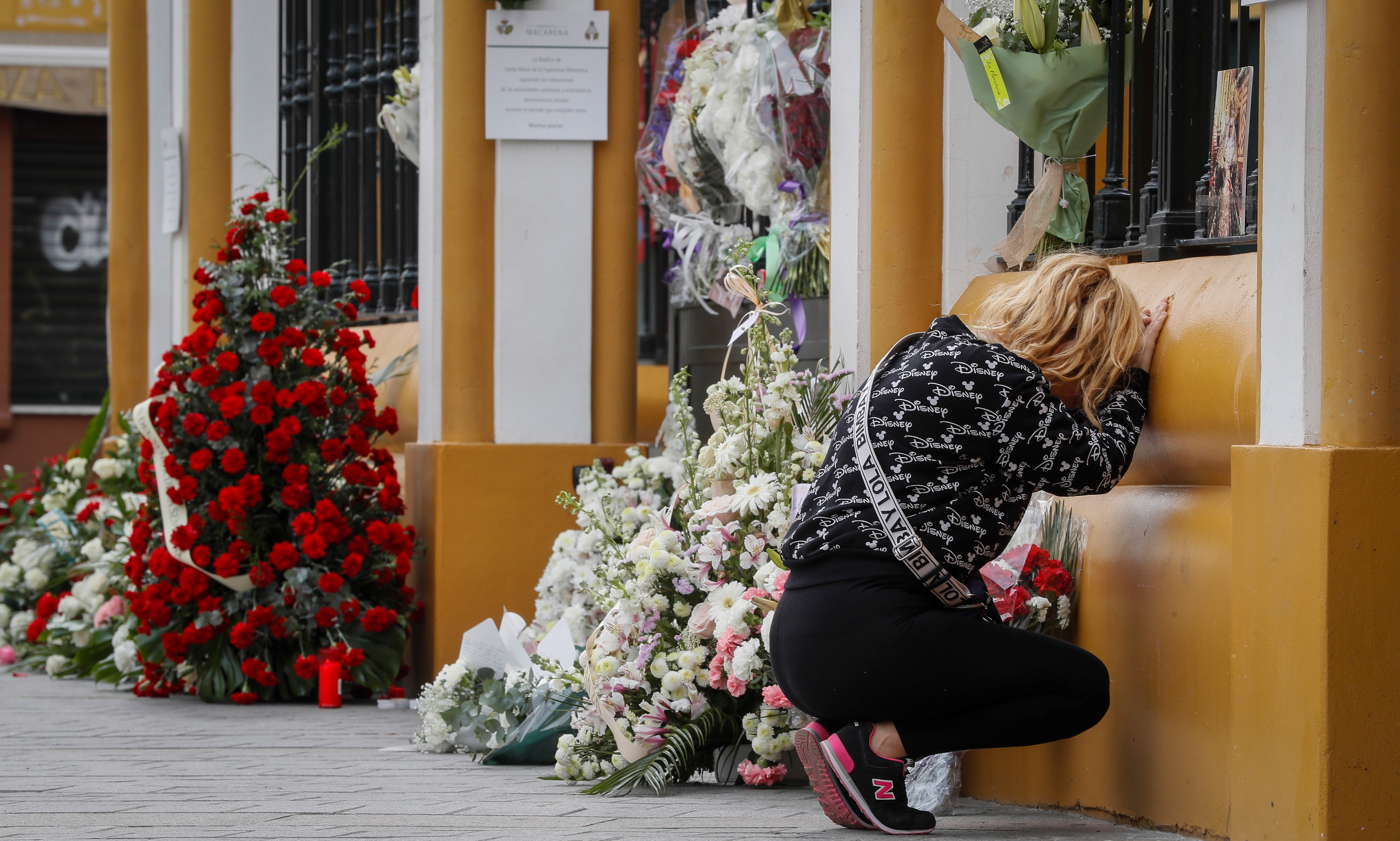 A woman prays next to some flowers laid in front of closed church in southern Spain.