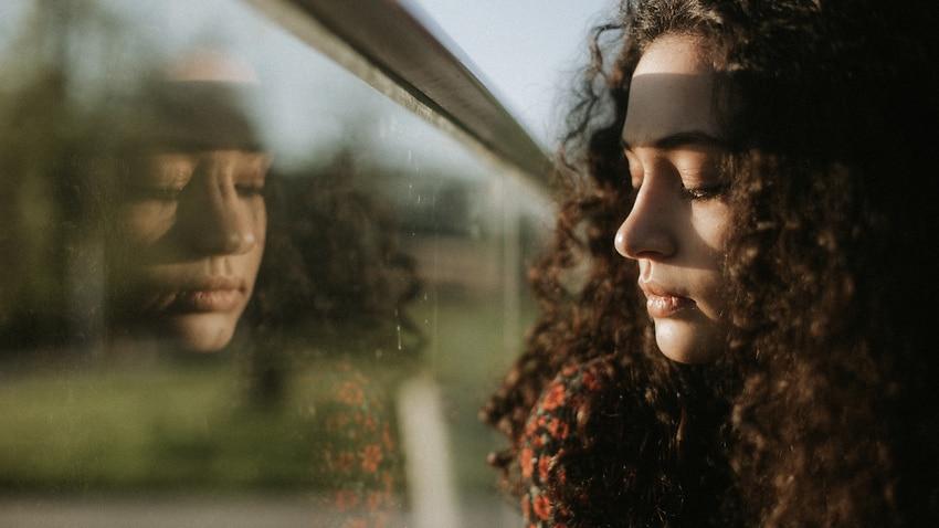 Stock photo of woman looking through window