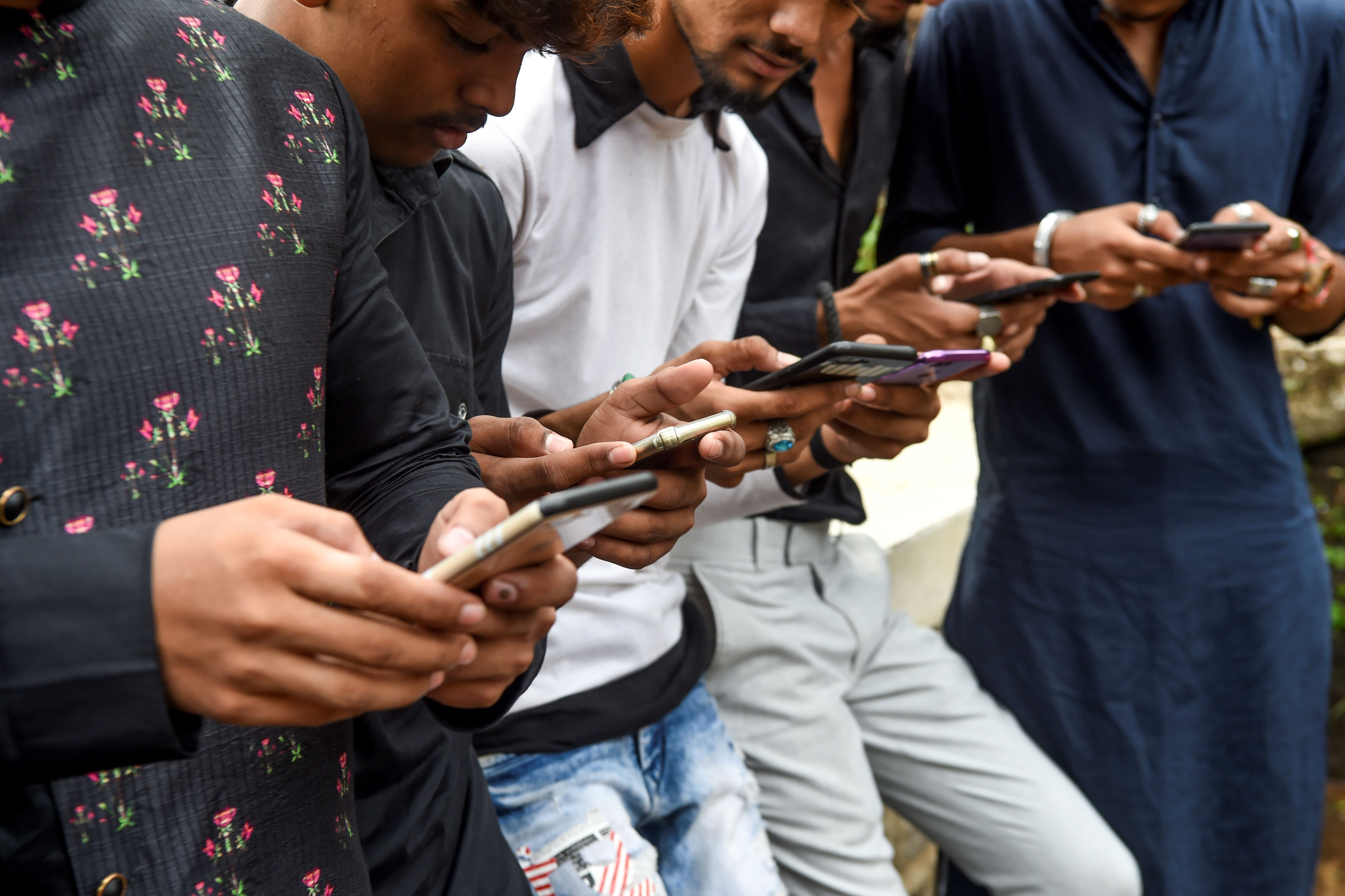 Youths watching videos on video-sharing app TikTok on their mobile phones in Mumbai.