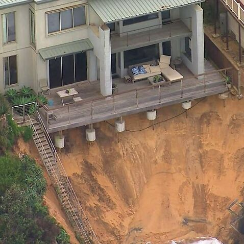 A house teeters on the edge after strong surf battered the coast.