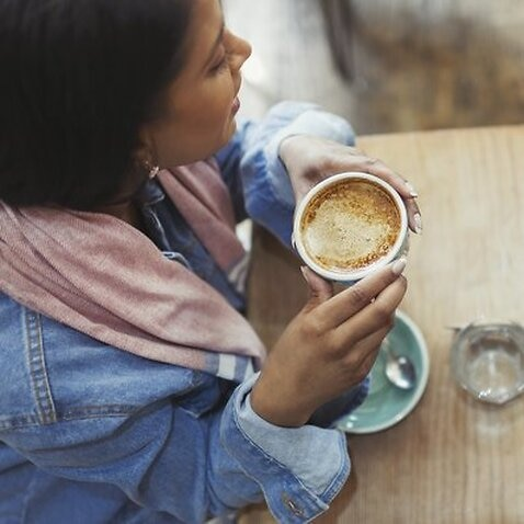 Female friends drinking coffee and using cell phone in cafe