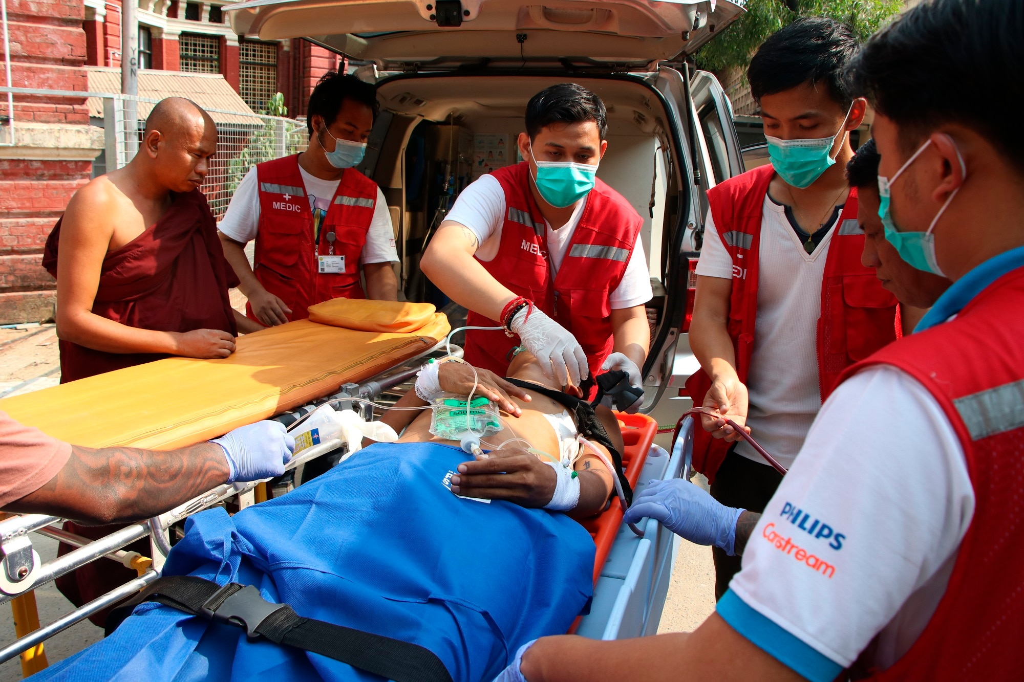 An injured anti-coup protester is brought in for medical treatment at a hospital in Latha township, Yangon, Myanmar.