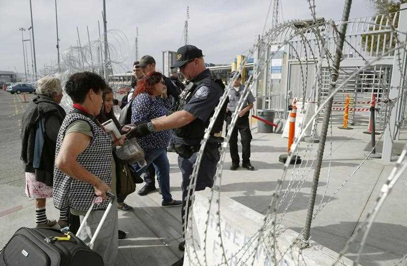 Migrants from Central America have their backgrounds checked in Tijuana on the Mexican side of the border with the United States.