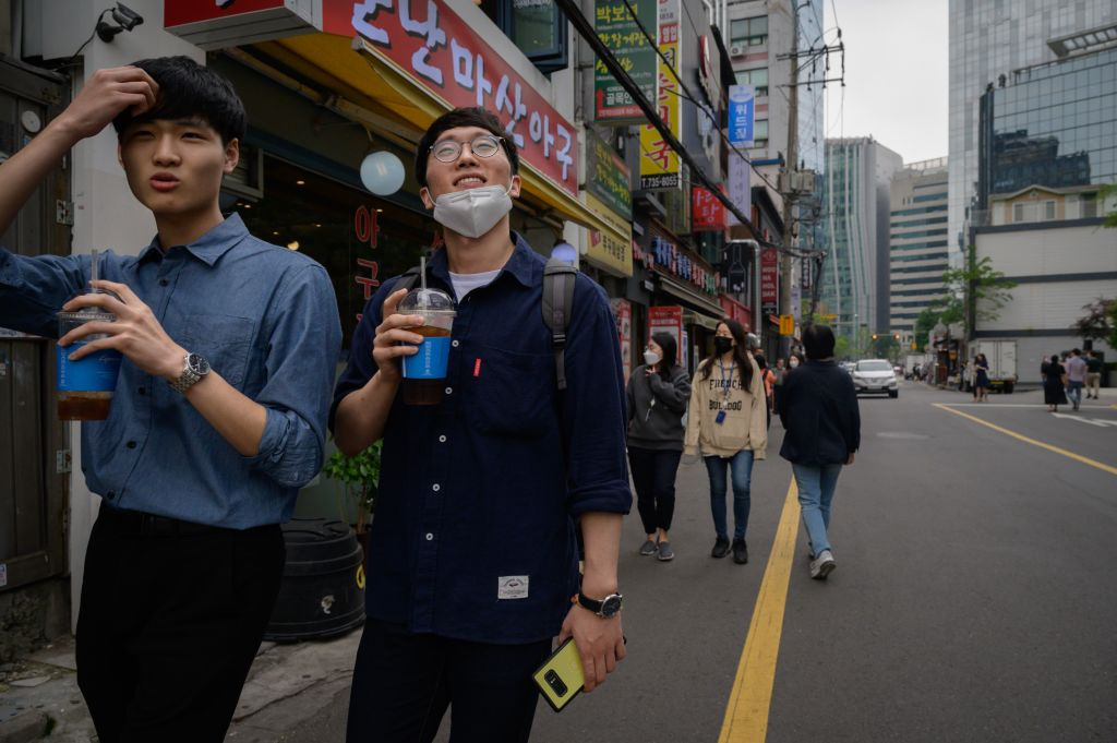 Office workers walk along a street during the lunch period in central Seoul