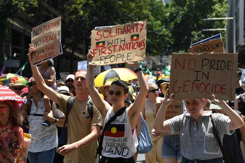 Sydney protesters hold signs aloft as they march. Thousands have rallied across Australia, demanding a change to the date of Australia Day.