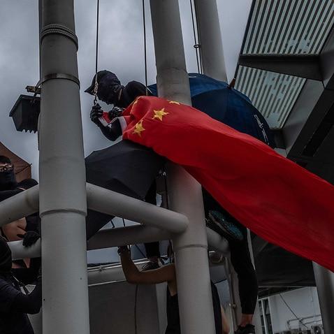 Protestors take down a national Chinese flag in Hong Kong.