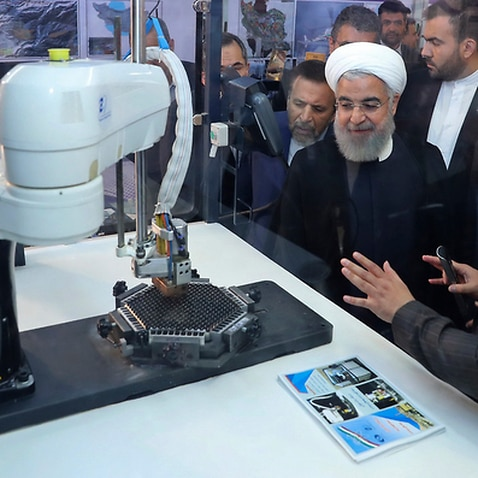 President Hassan Rouhani listens to explanations on new nuclear achievements at a ceremony to mark National Nuclear Day, in Tehran
