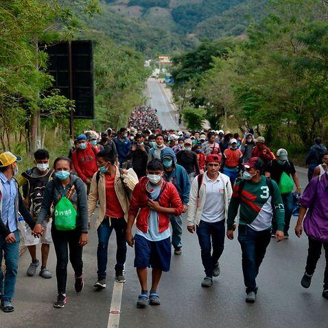 Honduran migrants, part of a caravan heading to the United States, walk along a road in Camotan, Guatemala on 16 January, 2021.