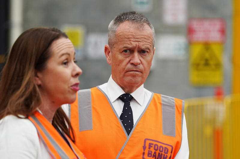 Federal Opposition Leader Bill Shorten looks on as Foodbank CEO Brianna Casey.