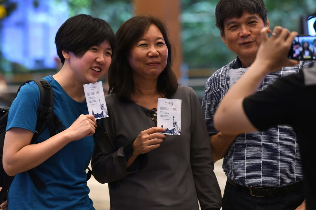 Passengers of flight SQ22, Singapore Airlines' inaugural non-stop flight to New York pose with souvenir cards.