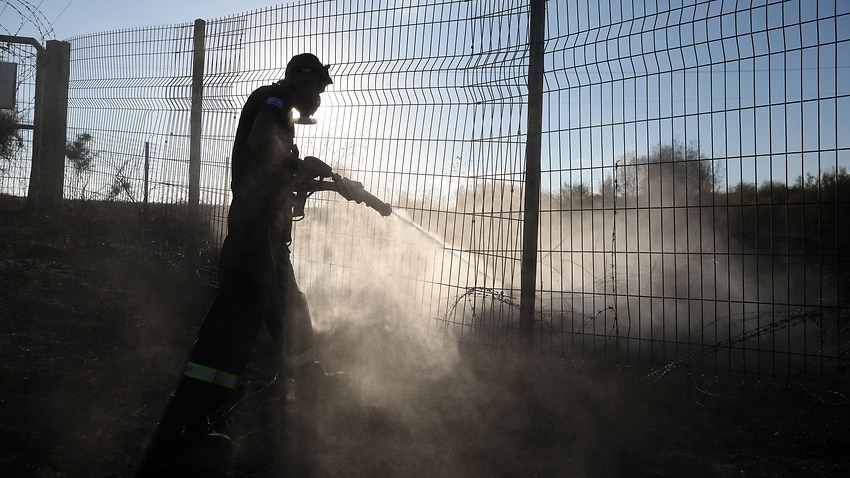 An Israeli firefighter tries to put out a fire near in field near Kibbutz Nir Am, close to the Israeli border with the Gaza Strip, 23 August 2020.