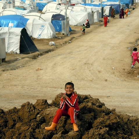 A Syrian Kurdish refugee plays on a pile of dirt in the Dumiz refugee camp in northern Iraq.