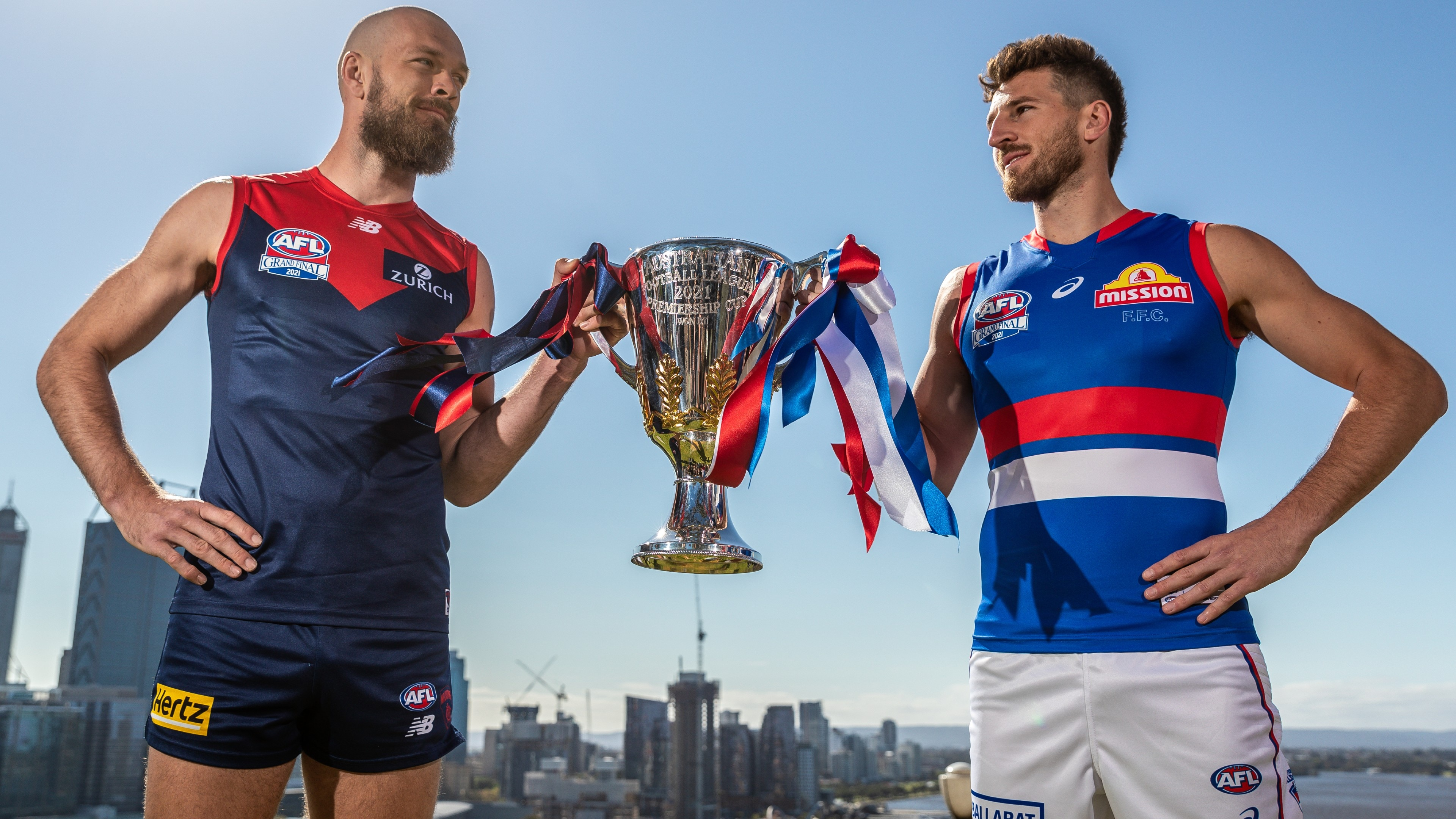 Max Gawn (L) captain of the Demons and Marcus Bontempelli, captain of the Bulldogs holding the 2021 AFL Premiership Cup after an AFL Grand
