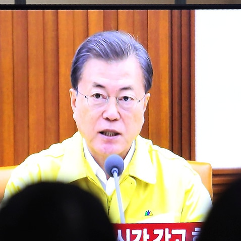 A TV screen shows South Korean President Moon Jae-in's speech during a news program at the Seoul Railway Station in Seoul, South Korea, Sunday, 23 February
