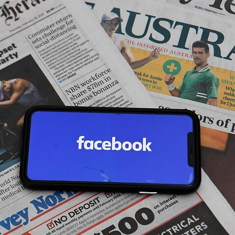 An illustration image shows a phone screen with the 'Facebook' logo and Australian Newspapers at Parliament House in Canberra, Thursday, February 18, 2021. Social media giant Facebook has moved to prohibit publishers and people in Australia from sharing o