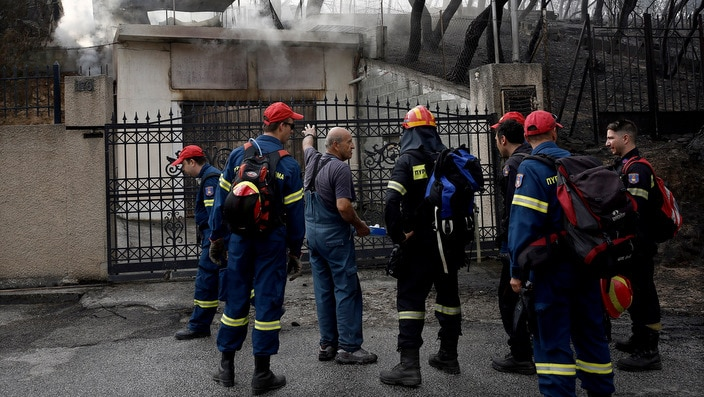 Firefigthers look for survivors by searching house by house in the area of Neo Voutza, northeast Attica, Greece.