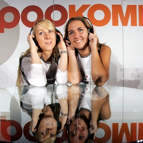 Hostesses Hannah and Janine pose with earphones in front of the logo of the Popkomm music trade fair in Berlin.